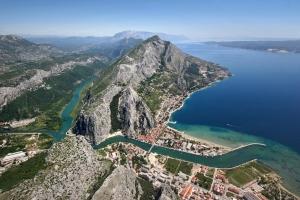 Luftbild von Omis das an der Mündung des idyllischen Flußes Cetina liegt. Im Hintergrund die Riviera von Makarska mit dem Biokovomassiv und die Insel Brac.